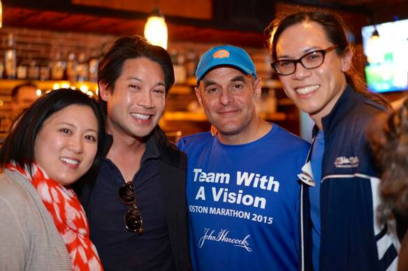 Vincent Hau and family meet NPR host and fellow Team With A Vision sighted guide Peter Sagal at an event Boston Marathon weekend